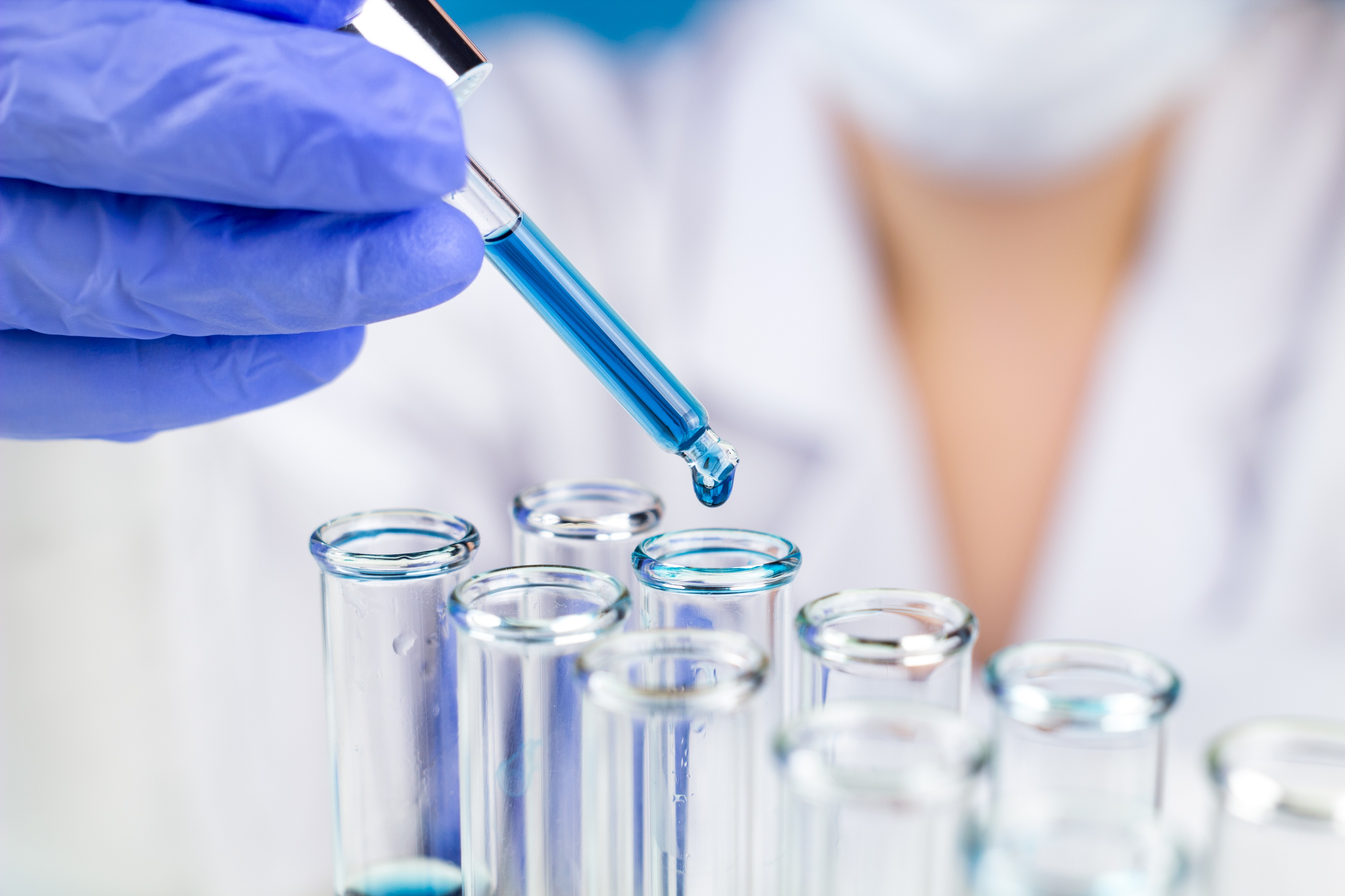 Sientist With Pipette Blue Water Drop In Test Tubes In Laboratory.